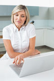 Casual woman using laptop in kitchen. Casual young woman using laptop in the kitchen at home Stock Photography