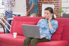Casual woman using laptop and mobile phone on couch Royalty Free Stock Photos