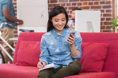 Casual woman using laptop and mobile phone on couch Stock Photography