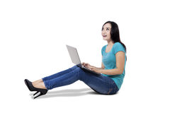 Casual woman using laptop sitting on floor Royalty Free Stock Image