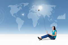 Casual woman using laptop on world map Stock Photography