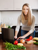 Casual woman using notebook while cooking lunch Royalty Free Stock Photography