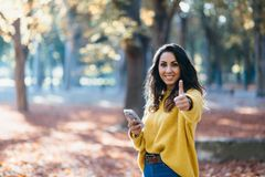 Casual woman using smartphone and doing thumbs up gesture in autumn stock images