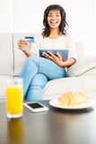 Casual woman using tablet while holding a card Stock Photography