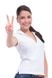 Casual woman victory sign. Casual young woman showing the victory sign while smiling at the camera. isolated on white background Stock Image