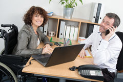 Casual woman in wheelchair working at her desk with colleague Royalty Free Stock Image