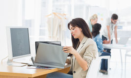 Casual woman working at desk with colleagues behind in office Royalty Free Stock Images