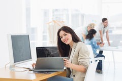 Casual woman working at desk with colleagues behind in office royalty free stock photography