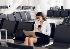 Casual woman working on laptop in airport hall. Woman waiting his flight at airport terminal, sitting on chair and stock photography