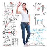 Casual woman writes calculations. Full length picture of a casual young woman writing calculations and graphs while holding her other hand in the pocket stock photos