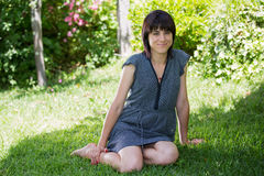 Casual woman. Young casual woman posing seated, smiling at the camera, outdoors Royalty Free Stock Photography