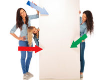 3 casual women pointing colored arrows to a blank billboard Stock Images