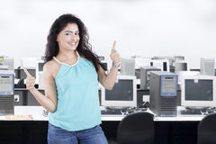 Casual worker with thumbs up in office Stock Photo