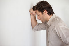Casual worried businessman leaning head on wall Stock Image
