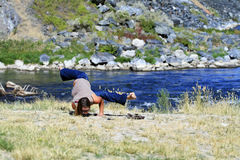 Casual Yoga. A young woman practices yoga casually by the river on a sunny day Royalty Free Stock Photos