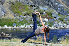 Casual Yoga. A young woman practices yoga casually by the river on a sunny day Stock Photo