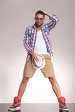Casual youn man holding his hat to his crotch Stock Image