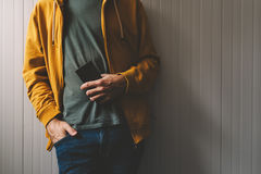 Casual young adult man posing with mobile phone in hand Stock Images