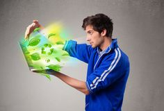 Casual boy holding laptop with recycle and environmental symbols Stock Image