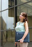 Casual young business woman with leather folder in downtown urba Royalty Free Stock Images