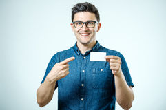 Casual young businessman holding business card. Casual young businessman holding and pointing business card. Isolated on gray Royalty Free Stock Image