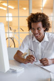 Casual young businessman sitting at his desk smiling at computer Royalty Free Stock Photo