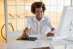 Casual young businessman using digitizer and headset at desk Royalty Free Stock Image