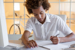 Casual young businessman writing at his desk smiling Stock Photo