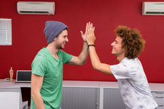 Casual young businessmen high fiving in office Stock Images