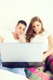 Casual young couple enjoying using laptop stock photos