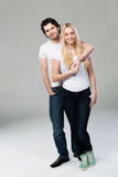 Casual young couple posing arm in arm Stock Photo