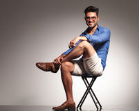Casual young fashion man sitting with his legs crossed. Full body picture of a casual young fashion man sitting with his legs crossed, smiling at the camera Stock Image