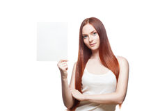 Casual young female with sign on white. Horizontal portrait of young attractive green-eyed red-haired caucasian female dressed in white casual clothing which Royalty Free Stock Photos