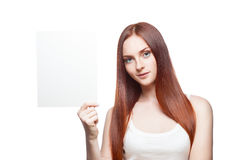 Casual young female with sign on white. Horizontal portrait of young attractive green-eyed red-haired caucasian female dressed in white casual clothing which stock photo