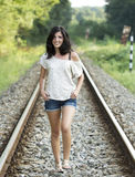 casual young girl walking on a railroad Royalty Free Stock Image