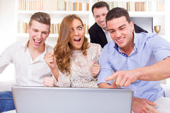 Casual young group of friends watching and cheering together at. Happy smiling casual young group of friends watching and cheering together at laptop Royalty Free Stock Photography