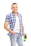 Casual young guy holding a bottle of beer and posing Stock Image