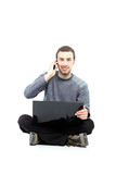 Casual young guy with laptop. A portrait of a male student working on a laptop isolated on white background Stock Images