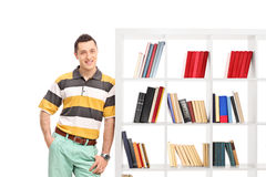 Casual young guy leaning against a bookshelf Royalty Free Stock Images