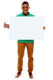Casual young guy pointing towards placard Royalty Free Stock Images