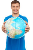 Casual young guy presenting globe Royalty Free Stock Images