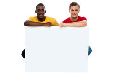 Casual young guys posing with blank billboard Royalty Free Stock Photos