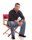 Casual Young Man. Seated in directors chair Royalty Free Stock Photo