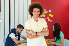 Casual young man with arms crossed in office Stock Images