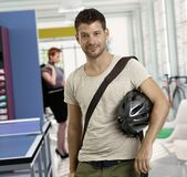 Casual young man arriving to work by bicycle. Casual young men at office arriving to work by bicycle stock photo