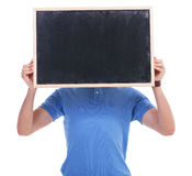 Casual young man with blackboard in front of face. Picture of a young casual man holding a blank blackboard in front of his face. isolated on a white background Royalty Free Stock Images