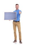 Casual young man with blackboard shows thumb up. Full length front view picture of a young casual man holding a blank blackboard and showing the thumb up gesture Stock Image