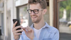 Casual Young Man Cheering Success on Smartphone Sitting in Outdoor Cafe stock video