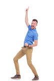 Casual young man cheers and points up Royalty Free Stock Photography