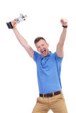 Casual young man cheers with trophy in hand Royalty Free Stock Photos